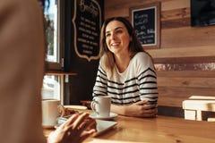 Amis s'asseyant dans un café et parler Photographie stock libre de droits