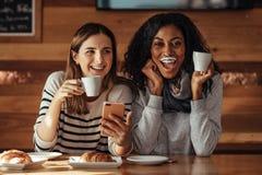 Amis s'asseyant dans un café potable de café Image stock