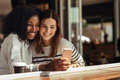 Amis s'asseyant dans un café prenant le selfie avec un téléphone portable Photographie stock