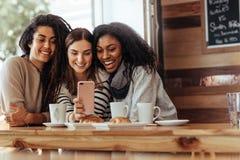Amis s'asseyant dans un café regardant le téléphone portable Photo libre de droits