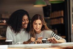 Amis s'asseyant dans un café regardant le téléphone portable Image stock