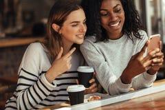 Amis s'asseyant dans un café regardant le téléphone portable Photos stock