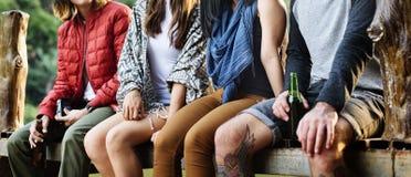 Amis s'asseyant dans un concept de rangée dehors Photographie stock