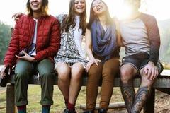 Amis s'asseyant dans un concept de rangée dehors Photo libre de droits