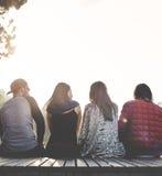 Amis s'asseyant dans un concept de rangée dehors Photo stock