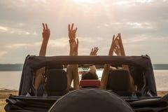 Amis s'asseyant dans une voiture avec des mains augmentées Photos libres de droits