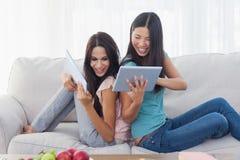 Amis s'asseyant de nouveau au dos se montrant leurs PCs de comprimé Images stock