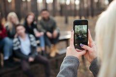 Amis s'asseyant dehors au foyer de forêt au téléphone Photos stock