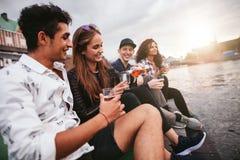 Amis s'asseyant dehors sur la jetée et ayant des boissons Photographie stock
