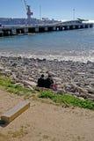 Amis s'asseyant devant la mer dans le port chilien Images libres de droits