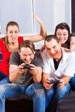 Amis s'asseyant devant le cadre de console de jeu Photo stock