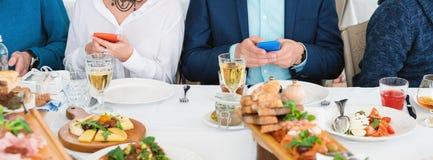 Amis s'asseyant en alcool de café, de consommation et de boissons tout en à l'aide des téléphones portables Foyer au téléphone, a Photo libre de droits