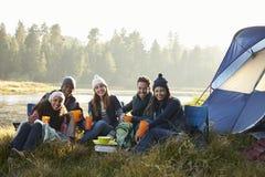 Amis s'asseyant en dehors d'une tente près d'un lac regardant à l'appareil-photo Photographie stock libre de droits