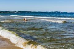 Amis s'asseyant en eau de mer Images libres de droits