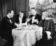 Amis s'asseyant ensemble à une table de dîner (toutes les personnes représentées ne sont pas plus long vivantes et aucun domaine  Photo libre de droits
