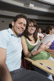 Amis s'asseyant ensemble dans la salle de classe Image stock