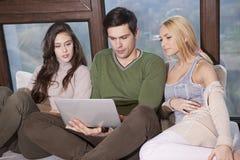Amis s'asseyant ensemble sur le sofa Image libre de droits