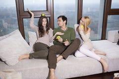 Amis s'asseyant ensemble sur le sofa Photographie stock