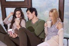 Amis s'asseyant ensemble sur le sofa et le café potable Image libre de droits