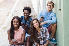 Amis s'asseyant ensemble utilisant le téléphone portable Image libre de droits