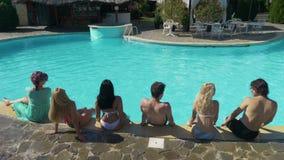 Amis s'asseyant par la piscine à une villa privée attendant la partie pour commencer clips vidéos