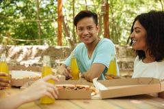 Amis s'asseyant par la table dans la forêt avec des boissons Image libre de droits