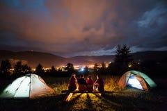 Amis s'asseyant près du camp et des tentes le soir Photographie stock libre de droits