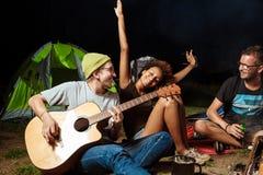 Amis s'asseyant près du feu, souriant, parlant, repos, jouant la guitare camper Images libres de droits