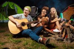 Amis s'asseyant près du feu, souriant, parlant, repos, jouant la guitare camper Image libre de droits