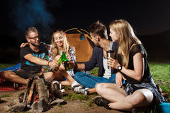 Amis s'asseyant près du feu, souriant, parlant, se reposant, ours potable camper Images libres de droits
