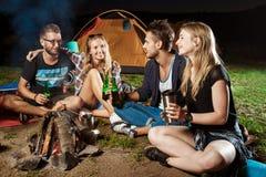 Amis s'asseyant près du feu, souriant, parlant, se reposant, ours potable camper Images stock