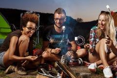 Amis s'asseyant près du feu, sourire, jouant la guitare Guimauve de gril de camping Photo stock