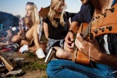 Amis s'asseyant près du feu, sourire, jouant la guitare Guimauve de gril de camping Image libre de droits