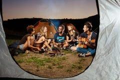 Amis s'asseyant près du feu, sourire, jouant la guitare Guimauve de gril de camping Images libres de droits
