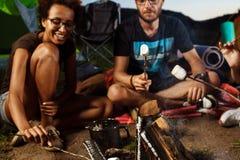 Amis s'asseyant près du feu, sourire, jouant la guitare Guimauve de gril de camping Photographie stock