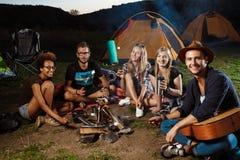 Amis s'asseyant près du feu, sourire, jouant la guitare Guimauve de gril de camping Photos libres de droits