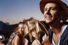 Amis s'asseyant près du feu, sourire, jouant la guitare Guimauve de gril de camping Photos stock