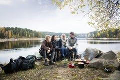 Amis s'asseyant sur au bord du lac pendant le camping Photos libres de droits
