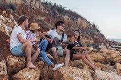 Amis s'asseyant sur des pierres sur la plage L'homme joue la guitare Image libre de droits