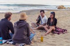 Amis s'asseyant sur des pierres sur la plage L'homme joue la guitare Images libres de droits