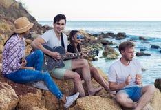Amis s'asseyant sur des pierres sur la plage L'homme joue la guitare Photo libre de droits
