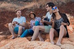 Amis s'asseyant sur des pierres sur la plage L'homme joue la guitare Photos libres de droits