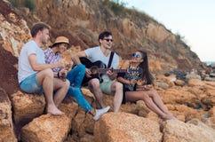 Amis s'asseyant sur des pierres sur la plage L'homme joue la guitare Images stock