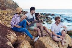 Amis s'asseyant sur des pierres sur la plage L'homme joue la guitare Photo stock
