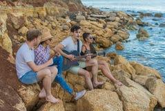Amis s'asseyant sur des pierres sur la plage L'homme joue la guitare Photographie stock libre de droits
