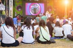 Amis s'asseyant sur l'herbe, appréciant un festival de musique d'extérieur Image libre de droits