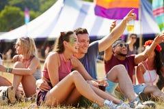 Amis s'asseyant sur l'herbe ayant l'amusement à un festival de musique Image stock