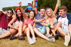 Amis s'asseyant sur l'herbe encourageant à un festival de musique Photo stock