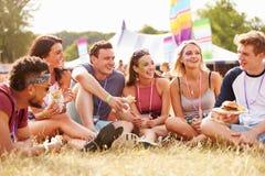 Amis s'asseyant sur l'herbe et mangeant au festival de musique Images stock