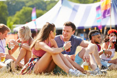 Amis s'asseyant sur l'herbe parlant au festival de musique Photos libres de droits